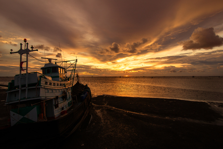 Fishing boat is on the sea water with sunset cloud and sky.