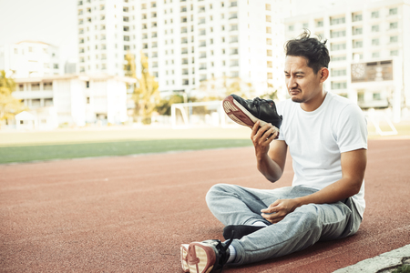 a man disgusted by the smell of his running shoe. A sport man sitting on the track race at stadium.