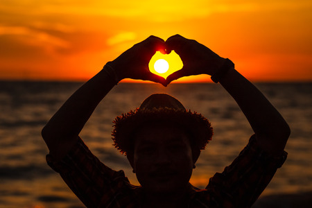 hands forming a heart shape with sunset silhouette. 写真素材 - 122677710