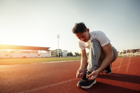 attractive brunette man enlacing him sport shoes on track race. A man at sport stadium with sunset. Stockfoto