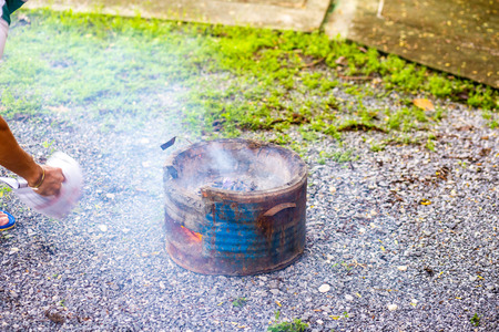Fill charcoal briquette to hot flaming charcoal in bbq grill stove. Burning charcoal for cooking barbecue food.