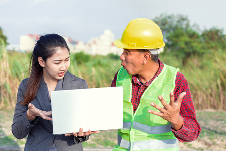 Men in hard hats and uniform with young woman. Team of architects, engineers discussing work. 写真素材