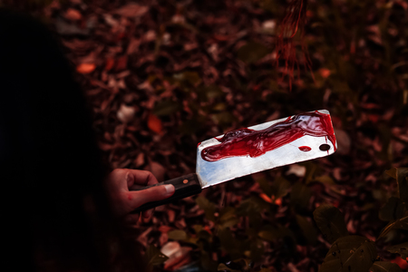 Woman holding knife with blood in the forest, halloween concept