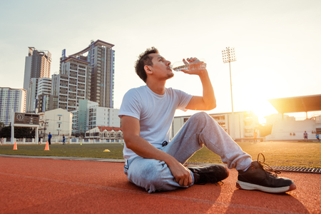 Caucasian man drinking water after exercises. Sport man sitting on track race at sport stadium and sunset.