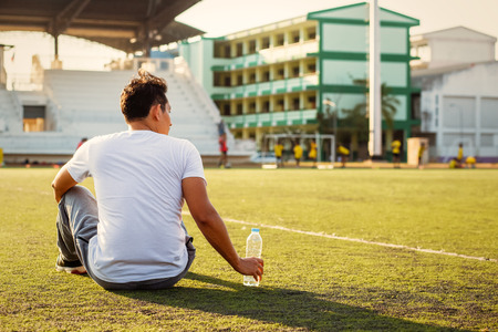 Thirsty man on grass at sport stadium and hand catch a bottle of pure water. Stock Photo