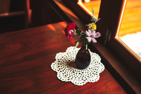 A flower in jar on the the wood table in coffee shop.