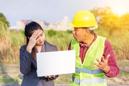 Men in hard hats and uniform with young woman. Team of architects, engineers discussing work. A women hold laptop.