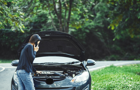 A women and broke down car on the road and she use mobile phone. 写真素材 - 123767718