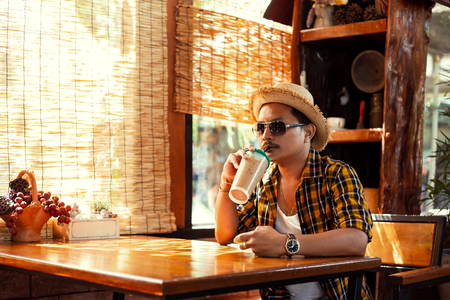 A man wear sunglasses and hat and drink ice coffee at summer. 写真素材