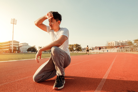 Tired wet athletic man wiping sweat his hand at sport stadium with sunset. 写真素材 - 123767725