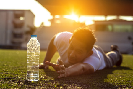 Thirsty man on grass at sport stadium reach for a bottle of pure water. 写真素材 - 123767730