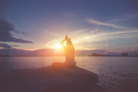 A women yoga on the rock near the sea with sunset sky. 写真素材 - 123767759