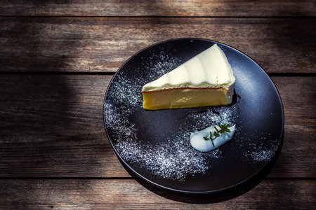 Slice of cheese cake stuffed with whipped cream in dish on the wood table. Stockfoto
