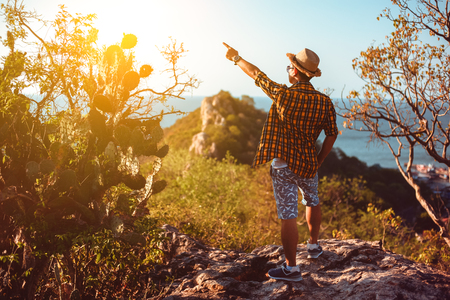 A travel man pointing on something with his hand. Man shows direct with his hand on top of cliff in summer mountains. Business travel and success concept. 写真素材