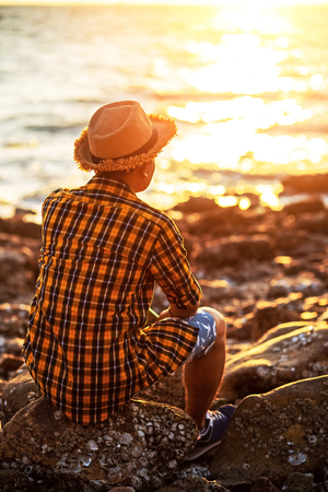 A man travel and  sitting on the stone near sea water and sunset in summer. 写真素材 - 123767765