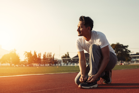 attractive brunette man enlacing him sport shoes on track race. A man at sport stadium with sunset. Stock Photo