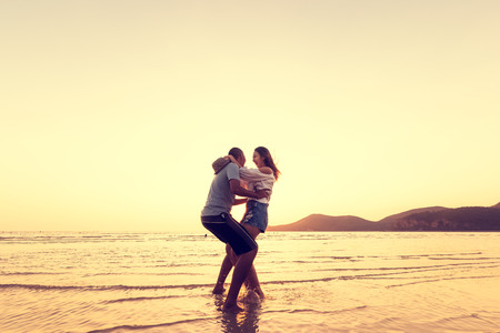 Couple in love having romantic tender moments at sunset on the beach. Imagens
