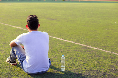 Thirsty man on grass at sport stadium after exercise. A bottle of pure water on grass near a man. Stockfoto