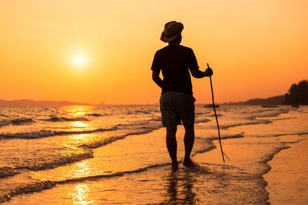 Young man walking on the beach. travel and relax concept.