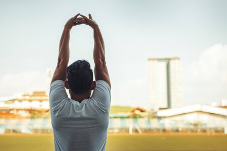 Full length portrait of a athletic man stretching in the morning and standing at sport stadium. 写真素材