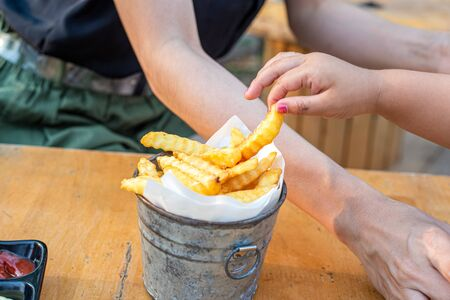 Children hands Picking French Fries on wood table. 写真素材