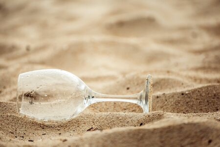 wine Glass on sand in the beach.