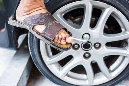Mann wechselt Reifen mit Radschlüssel Standard-Bild