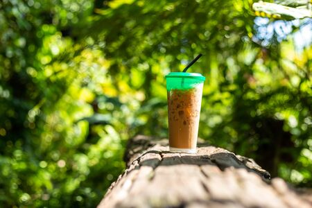 ice coffee on the wood table in the forest. 写真素材