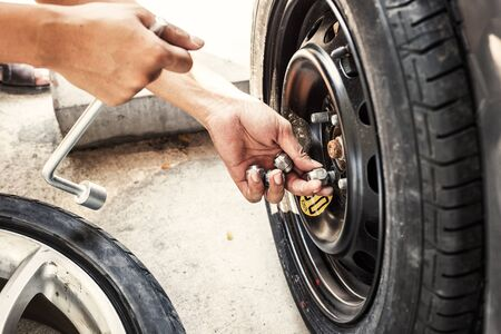 Hands of mechanic pick up the nut of car wheel.Change a flat car tire at car park with Tire maintenance, damaged car tyre.