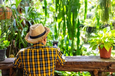 A man wear hat and sitting on wood char at garden and relaxing.