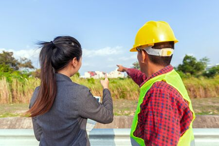 Businesswoman and foreman talking together. Engineer and manager teamwork and checking at site construction .