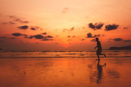 A man running at island and him running on the beach with sunset and beautiful sky with nice cloud. 写真素材