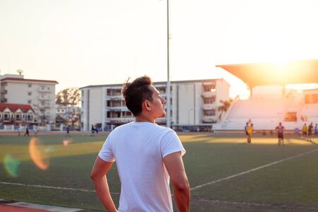 A sport man standing in racetrack at sport stadium with sunset. Sport concept.