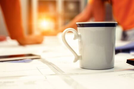 A coffee cup on white paper between business meeting together.