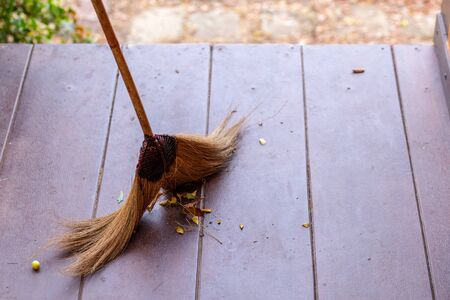 Sweeping dry leaves with broom.fall season.Sweep the leaves, .Maintenance worker in park garden cleans the floor.