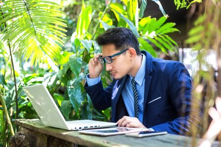 businessman is using eyeglasses  text from screen notebook computer. A man  has short sighted, 写真素材
