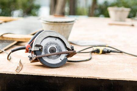 Circular saw on wood board at construction building.