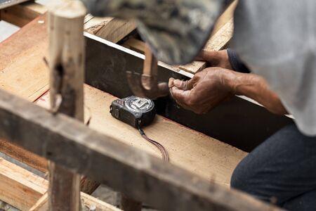Zimmermann arbeitet mit Hammer und Meter am Bau Standard-Bild