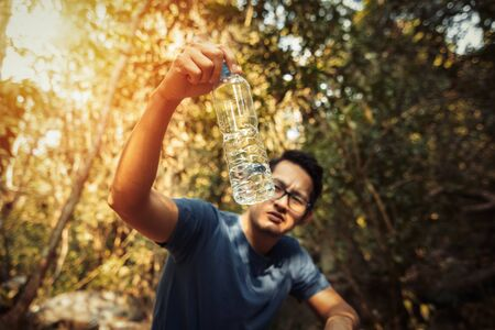 A man show few water in bottle in the forest and hot weather.