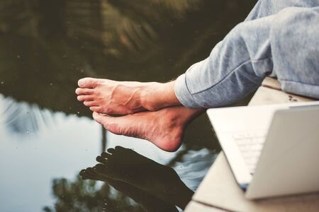 A man sitting near the water. Foots over the water. Relaxing concept. 写真素材