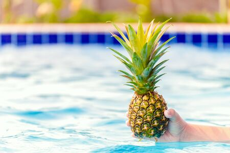 hand hold pineapple in the blue water.