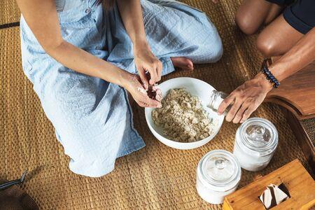 Women hand thresh flour in enameled bowl for make cooking dessert.