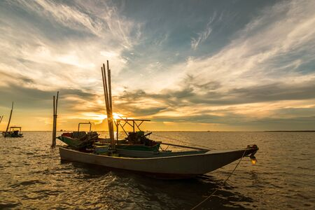 wood fishing boat in the sea and sunset.