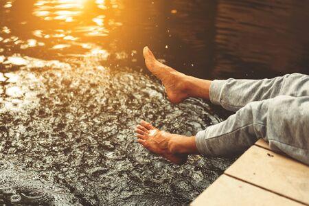 relax man at a lake having fun and splashing water in summer