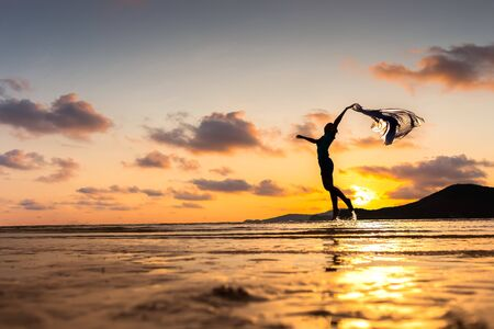 Happy woman jumping on the beach and water splash. Mountain, sea water and beautiful cloud is landscape. 写真素材
