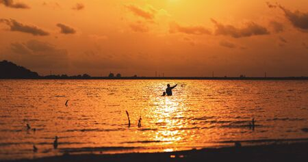 Two fisherman try catch a fish by trap in the water at sunset. 写真素材