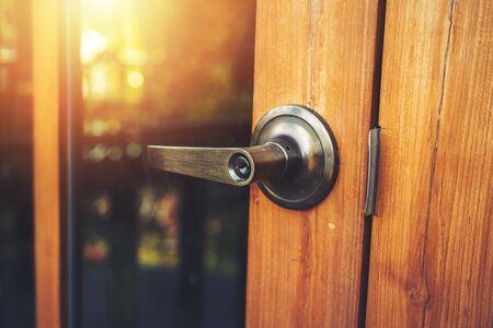 Pomo de la puerta en la puerta de madera y luz de sol.