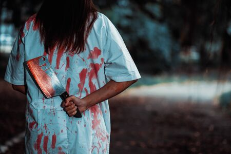 Woman holding knife with blood in the night park, halloween concept