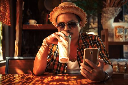 A man wear sunglasses and hat and drink ice coffee in summer.Hands use mobile phone with light of sun. 写真素材