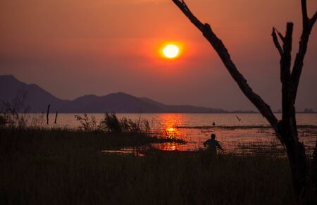 a man in wood fishing boat in the water and sunset. 写真素材